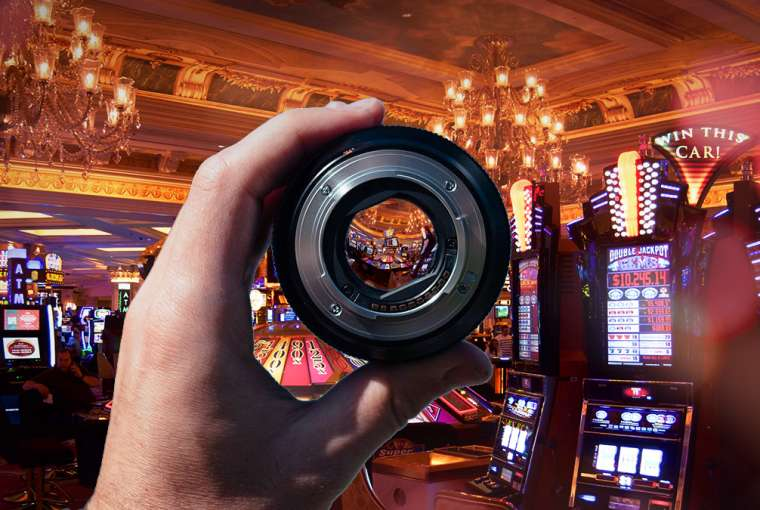 Tangan Memegang Lensa Kamera di Mesin Slot Kasino