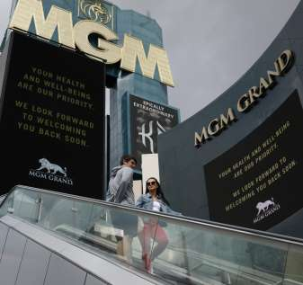 """The MGM Grand hotel-casino, which is closing, flashes messages on their marquees that read """"Your health and well-being are our priority. We look forward to welcoming you back soon."""" Monday, March 16, 2020, in Las Vegas. MGM Resorts International and Wynn Resorts will close their Las Vegas properties as of March 17 in light of the coronavirus pandemic. For most people, COVID-19 causes only mild or moderate symptoms, such as fever and cough. For some, especially older adults and people with existing health problems, it can cause more severe illness, including pneumonia. (AP Photo/John Locher)"""