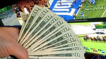 Tangan Memegang Uang Kertas 20 Dolar Dengan Latar Belakang TV Sportsbook