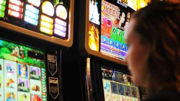 A woman plays the pokies.