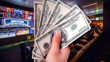 Tangan Memegang Uang Seratus Dolar Dengan Latar Belakang Sportsbook