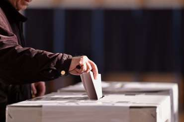 hand placing vote in ballot box