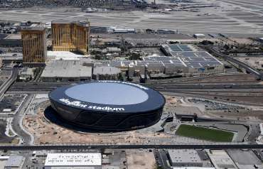 LAS VEGAS, NEVADA - MAY 21: (L-R) An aerial view shows Delano Las Vegas at Mandalay Bay Resort and Casino and Mandalay Bay Resort and Casino on the Las Vegas Strip east of the construction continuing at Allegiant Stadium, the USD 2 billion, glass-domed home of the Las Vegas Raiders on May 21, 2020 in Las Vegas, Nevada. Natural grass turf now covers the large field tray that sits on rollers that will move the field in and out of the stadium. The Raiders are scheduled to play their first preseason game at the 65,000-seat facility on August 27 against the Arizona Cardinals. (Photo by Ethan Miller/Getty Images)